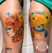 рыжеволосая девушка цветы и птица на бедре фото татуировок