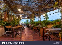 typical italian rooftop restaurant wooden tables in tuscany with covered roof pergola vine canopy with empty