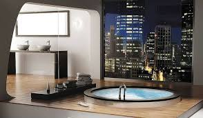 fascinating luxury bathroom idea with leveled floor with round undermount bathtub and wooden floor also washbowl sinks over wooden table and mirror and