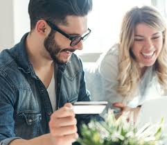 a couple in their bright home laugh as they look at their credit card and