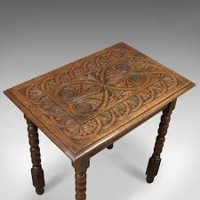 antique side table with carved decoration english oak 1908