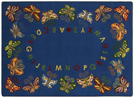 an heirloom quality classroom rug that features gentle erflies over a navy blue background the alphabet in matching earth tone colors is displayed in