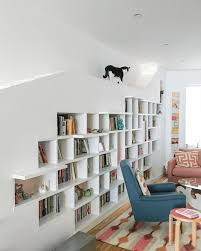 in the living room there s a custom bookcase wall with ramps for the two cats