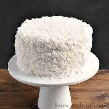 a coconut cake recipe made with fresh coconut on a white cake stand