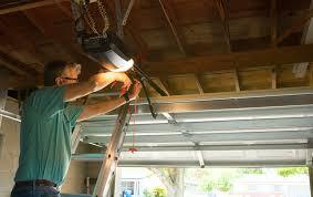 man fixing his garage door to avoid burglars