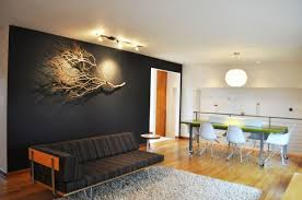 black wall black chaise lounge willow branches pendant light white stool lightwood floor ceiling lights rug