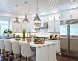 View in gallery Dazzling pendant lights above a white kitchen island with  dark granite top