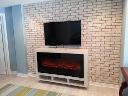 amantii bi 50 electric fireplace in black glass mounted in a custom floating cabinet
