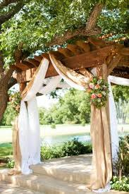 burlap wedding arbor. Burlap draping with country pink and green flowers over a wooden
