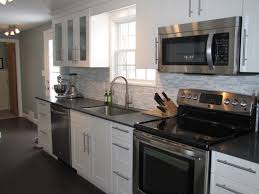 tasteful white mosaic backsplash also wall mounted white cabinets over black tiled countertops as inspiring white galley kitchen ideas