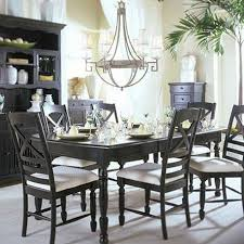 rustic dining area with chandelier black cabinet black table with candle and glass with black chairs image