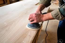 man sanding wood with orbital sander in a work stock photo 88312972