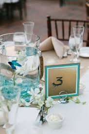 Table numbers drawn in sand with orchid, sea glass, and Beta fish  centerpieces.