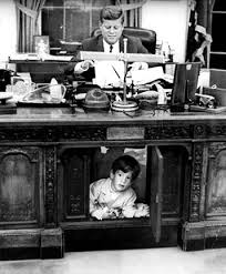 the oval office desk. john f. kennedy, jr. under the resolute desk in oval office. office