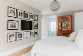 black mounted tv on white wall surrounded by photo frames ina comfort bedroom along with big