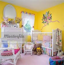 children s bedrooms baby room white crib changing table white wicker drawers and rocker yellow paint pink accents white lace curtains painted flower