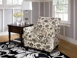traditional floral printed fabric accent chair with arm on black and white patterned rug also dark wooden end table drawer patterned accent chairs h17