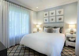 white and blue bedroom with framed black sea fans over headboard