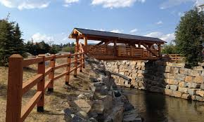 a pedestrian timber frame wooden bridge with a metal roof spans mark creek in
