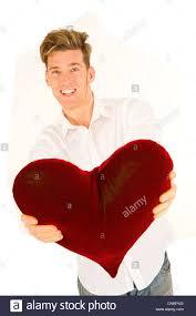 Man Shaped Pillow Young Man Handing A Heart Shaped Pillow Stock Photo Royalty Free
