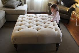 large square tufted ottoman coffee table with white upholstered cover and wooden legs on gray carpet tiles in living room ideas