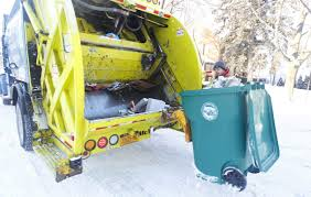 john schmidtz empties a recycling tote on a modern corp recycling truck at curbside pickup in