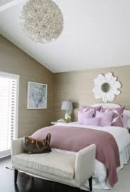 Purple and taupe bathroom features walls clad in taupe grasscloth lined  with a white flower mirror