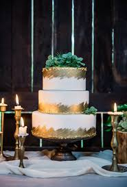 White And Gold Wedding Cake Topped With Greenery Brides