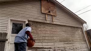 low angle medium shot boy shooting basketball at hoop over garage l69