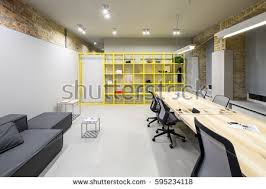 loft style office. office in loft style with gray and brick walls there are glowing lamps dark
