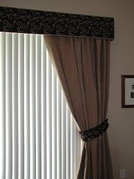 Cornice with one way draw drapes and vertical blinds on glass slider doors