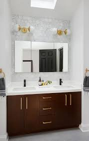 Under a skylight, gray wood like floor tiles lead to a brown dual washstand  accented