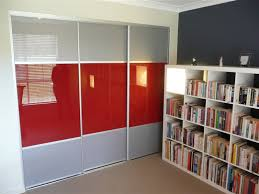 a bedroom with a bookcase which has a set of three doors the middle