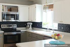 white painted cabinets with black tile backsplash