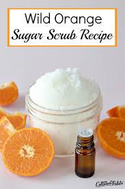 wild orange sugar scrub recipe shown in glass jar with oranges around it