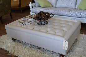 stunning living room with comfy pattern sofa and extra large white leather ottoman coffee table on white fur rug
