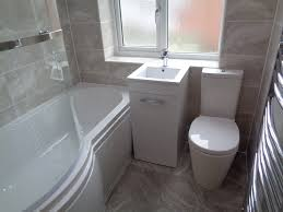 bathroom fitted with grey wall and floor tiles