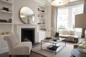 round mirror with brushed nickel frame over a simple modern white fireplace mantel built in shelving