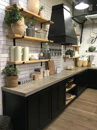 a rustic industrial kitchen with black cabinets and concrete countertops plus touches of light colored