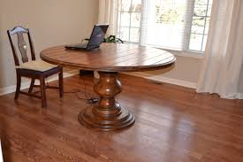furniture round brown wooden table with carved brown wooden pedestal base added by brown wooden
