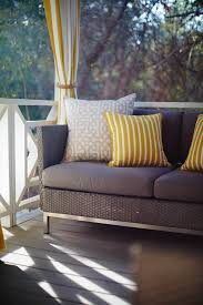 outdoor sofa with yellow and grey decorative throw pillows and yellow and white striped dry