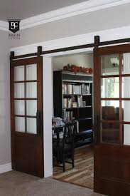 grandiose half glass 8 panels double barn doors interior with iron hardware as well as black open cabinet and vintage furnishings in traditional house