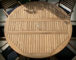 table top detail of 72 teak round table and slat back stack chair set shown with optional navy cushions