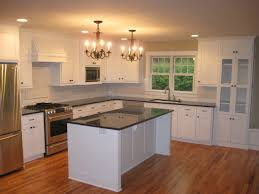 contemporary maple kitchen cabinets in white with black marble countertop and black knobs also black pulls
