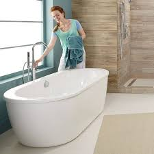 woman turning on faucet to fill the freestanding tub