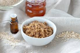 face sugar scrub shown on linen tablecloth with oats around the bowl and honey and essential