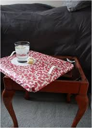 this repurposed sewing bench makes a daring side table with sufficient storage space which top is removed to srrve as serving tray or a nice lap desk