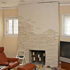 partially painted brick fireplace using a base coat drying then adding another color for
