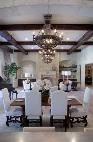 similar white furnishings with contrasting dark ceiling beams chandeliers and table