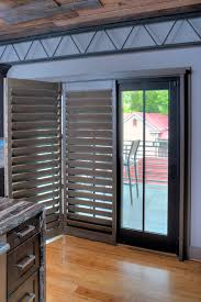 the bifold shutters fold on the side of the glass doors to allow for full functioning of the sliding patio doors